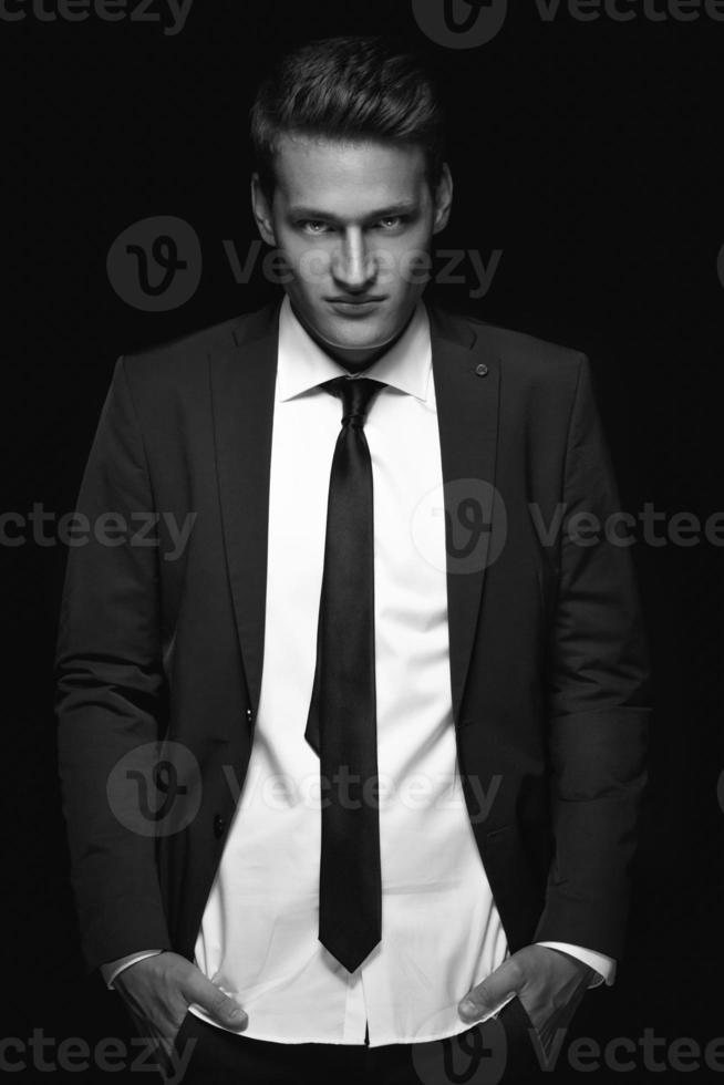 cool homme d'affaires debout sur fond sombre photo