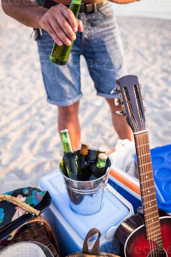homme ouvrant une bouteille de bière sur la plage. photo