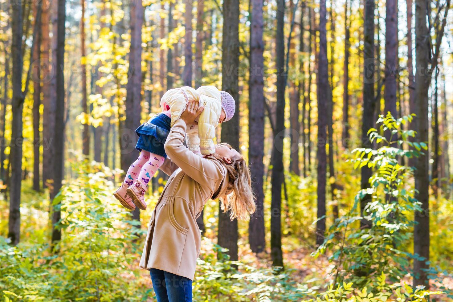 mère de famille heureuse et petite fille jouant sur la marche d'automne photo