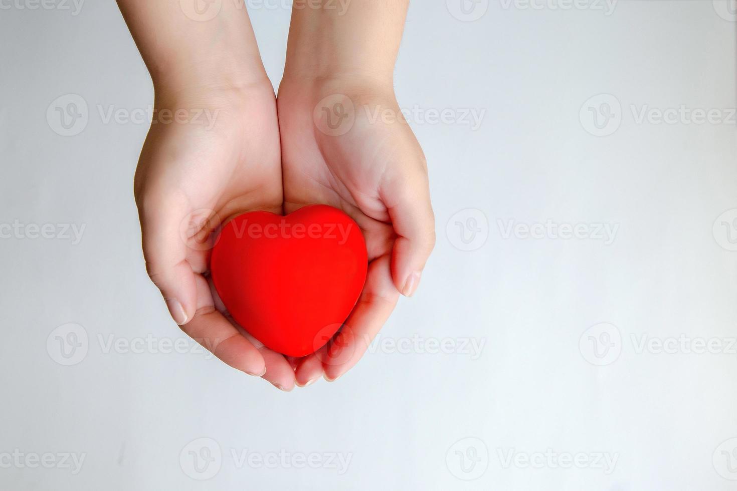 mains tenant coeur rouge isolé photo