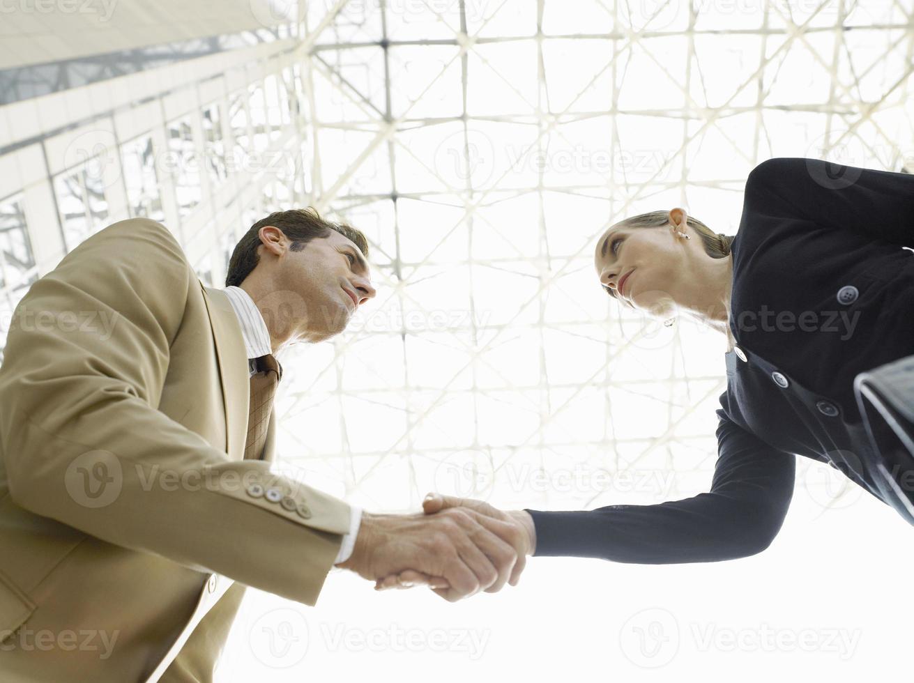 hommes d'affaires confiants se serrant la main contre le plafond photo