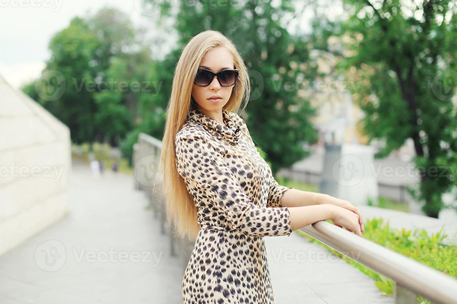 Belle jeune femme blonde vêtue d'une robe léopard et sunglas photo