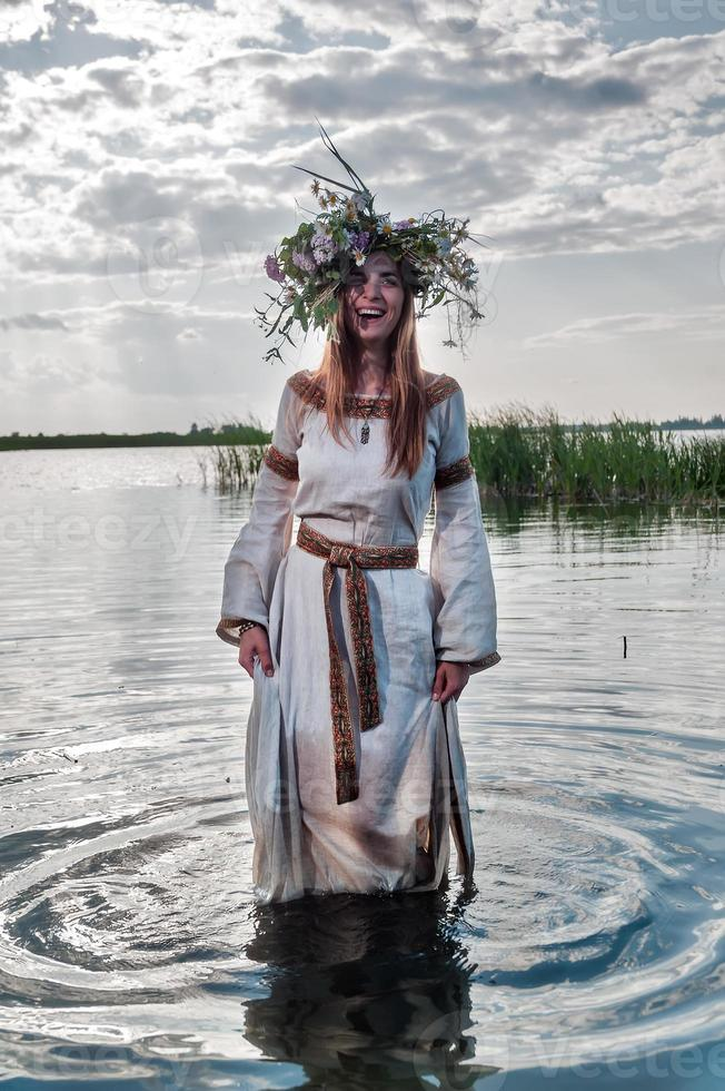 belle femme avec une couronne de fleurs se tient dans l'eau photo