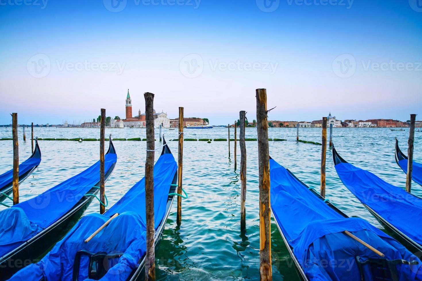 Venise, gondoles ou gondole au coucher du soleil et église en arrière-plan. photo