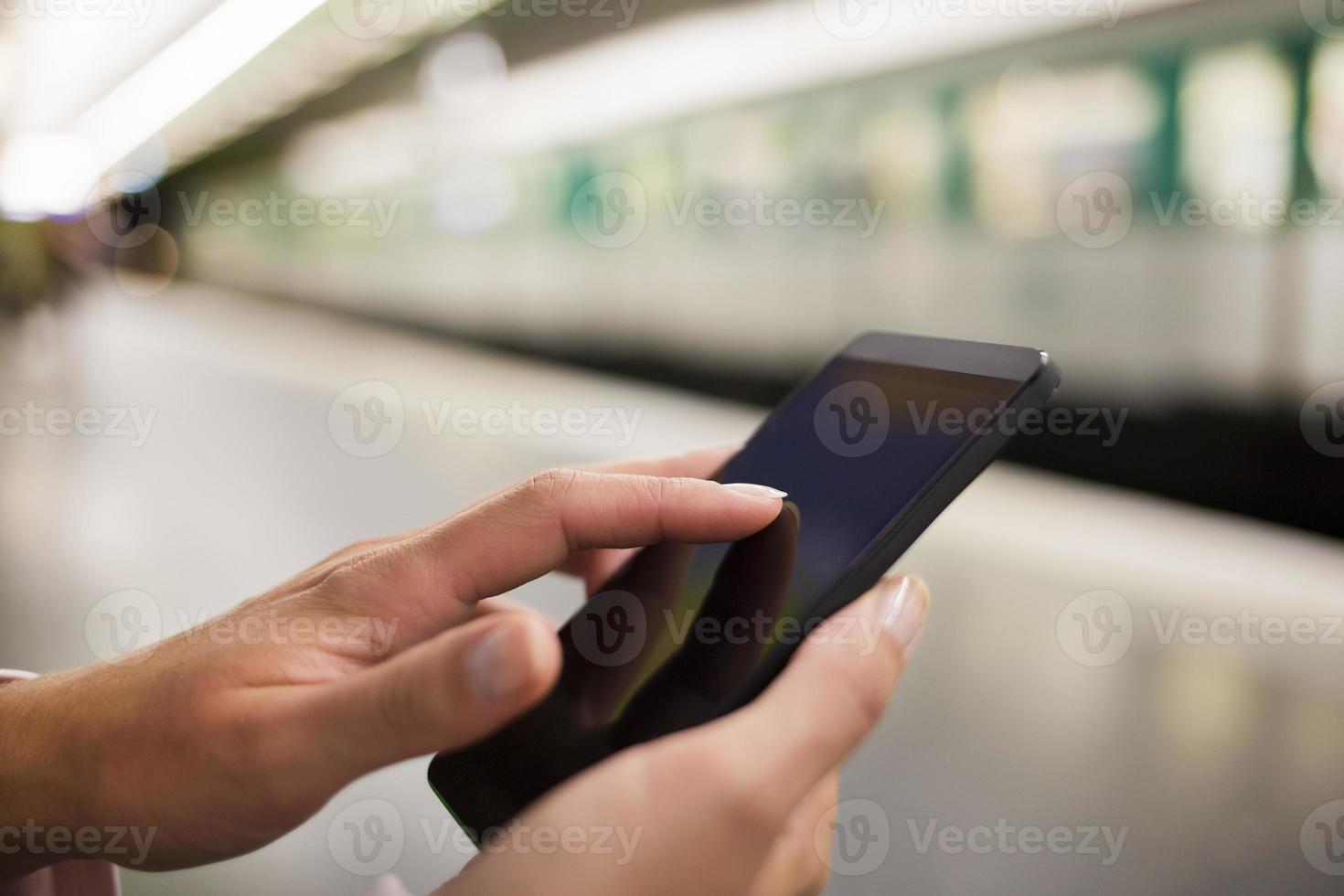 femme utilisant son téléphone portable sur la plate-forme du métro photo