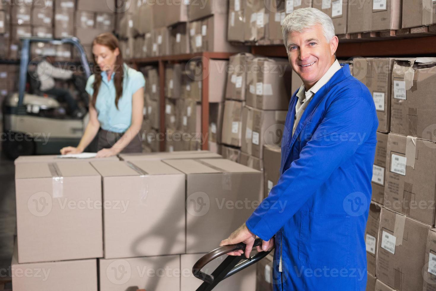 contremaître d'entrepôt souriant à la caméra avec chariot photo