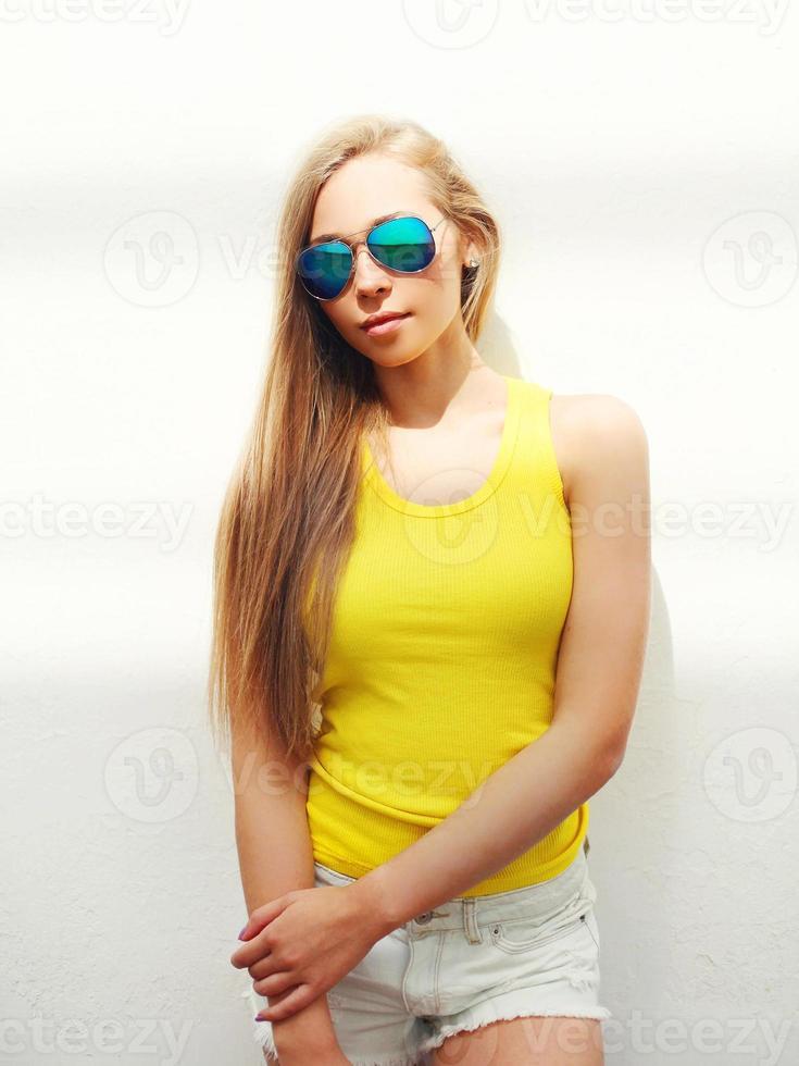 jeune jolie fille portant des lunettes de soleil et un t-shirt en ville photo