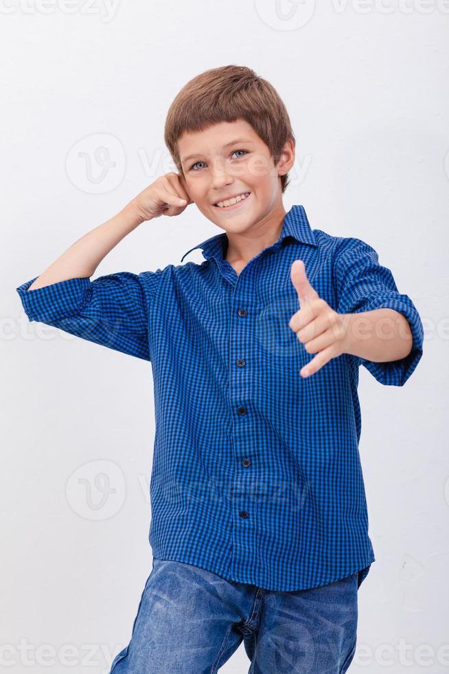 Heureux jeune garçon avec geste d'appel sur fond blanc photo