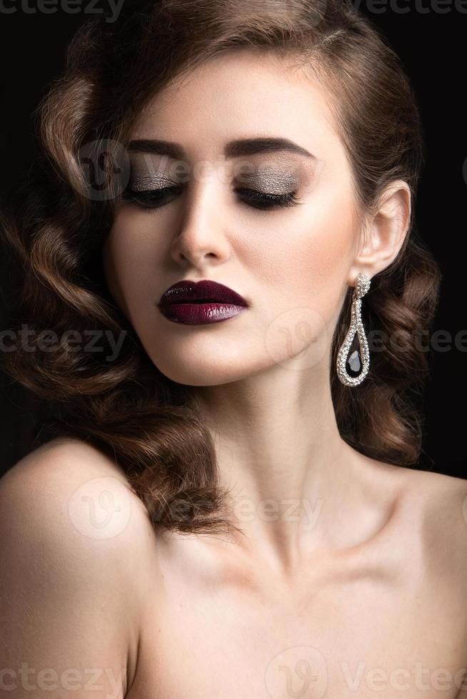 belle femme avec maquillage de soirée, lèvres bordeaux et boucles. photo