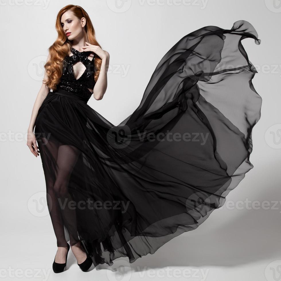 femme de mode en robe noire flottante. fond blanc. photo