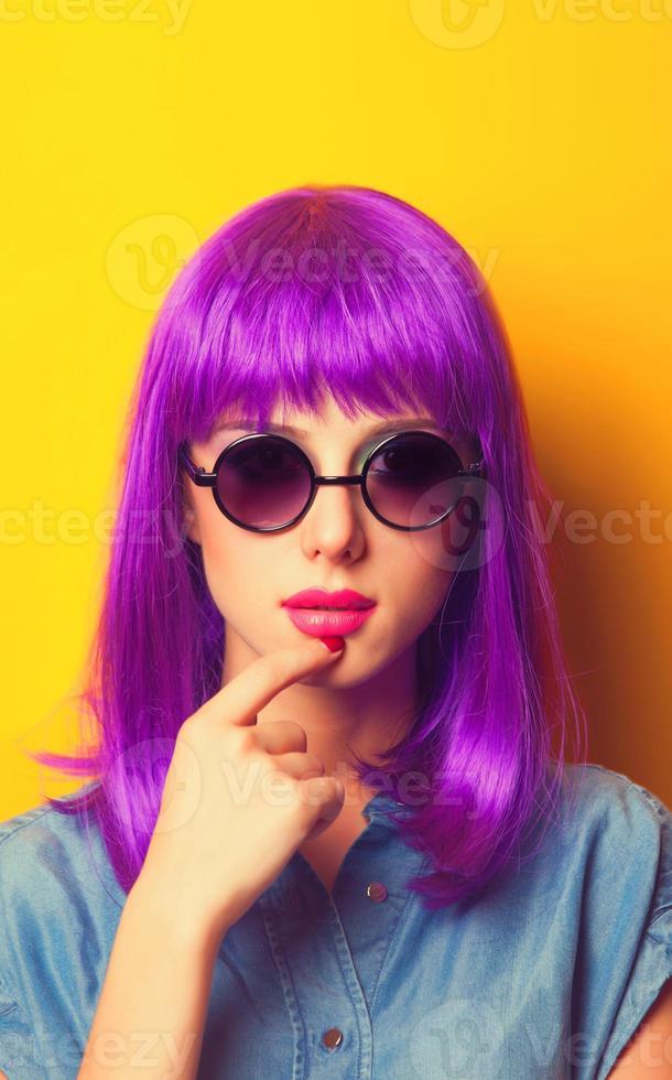 belle fille aux cheveux violets dans des lunettes de soleil sur backgrou jaune photo