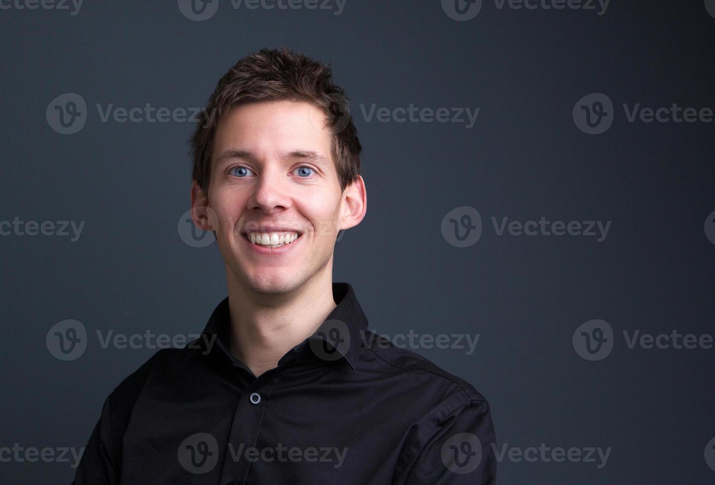 homme souriant, posant sur fond gris photo