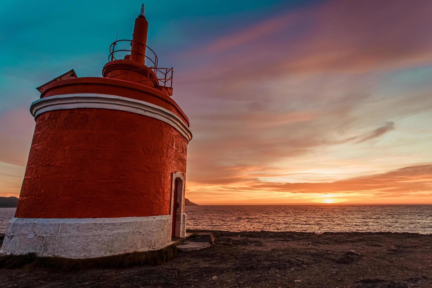 ciel coloré et un phare rouge photo