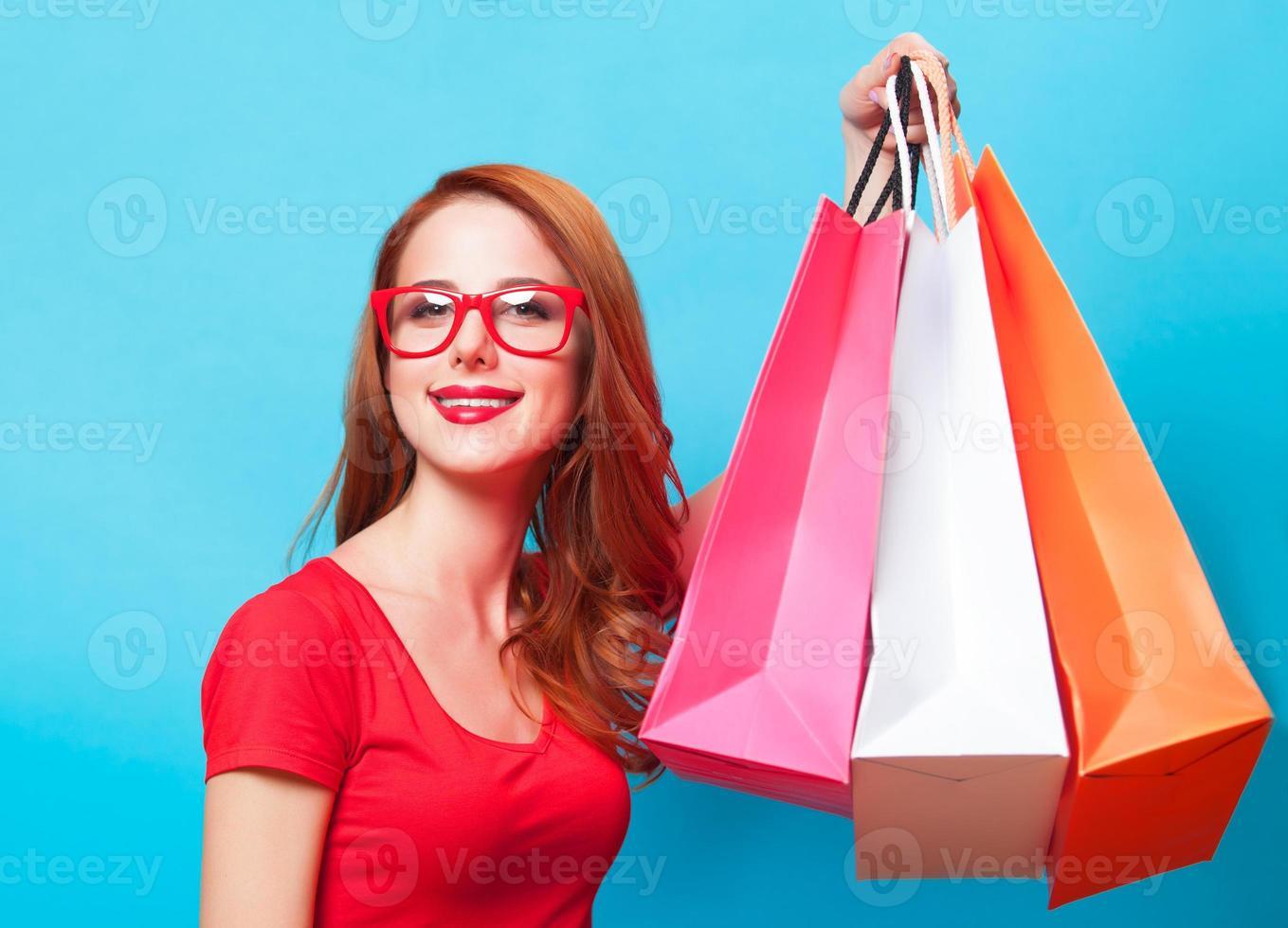 fille rousse avec des sacs à provisions sur fond bleu. photo