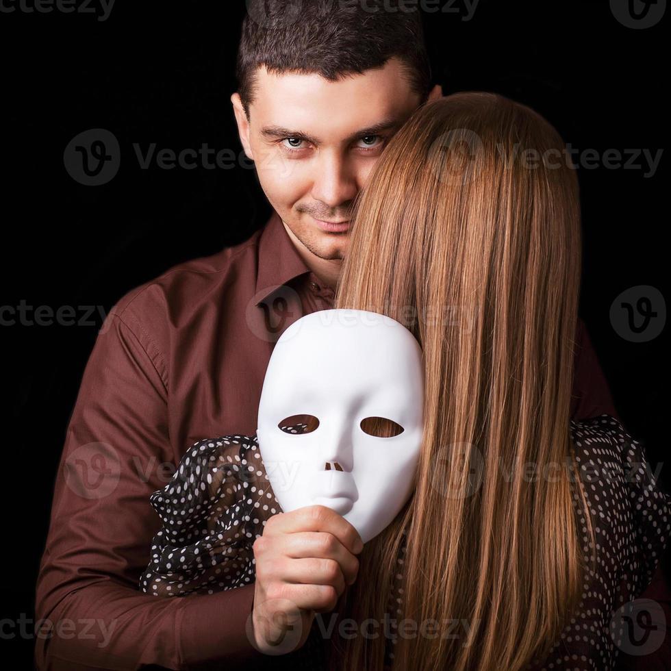 homme de mode tenant un visage de masque blanc. concept psychologique. photo