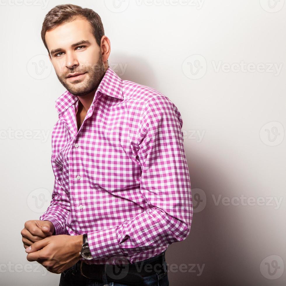 élégant jeune bel homme en chemise colorée lumineuse. photo