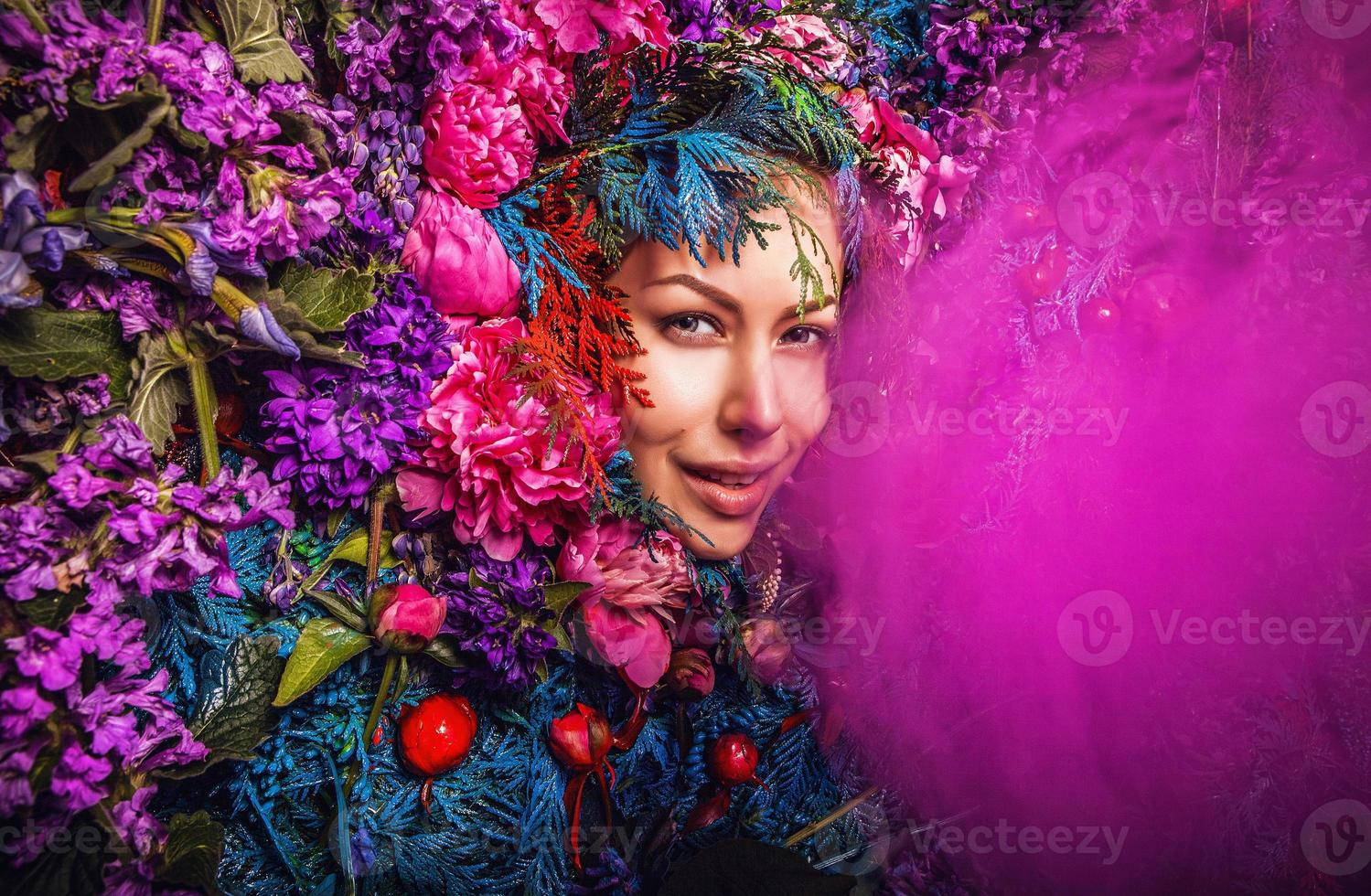 portrait de fille de conte de fées entouré de plantes et de fleurs naturelles. photo