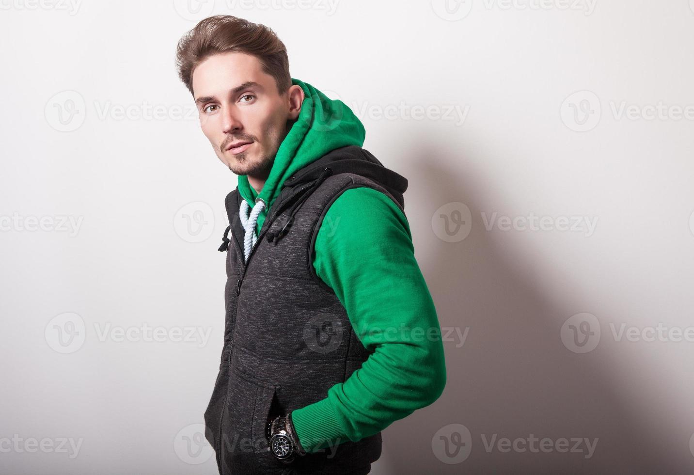 séduisant jeune homme en gilet gris et pull vert. photo
