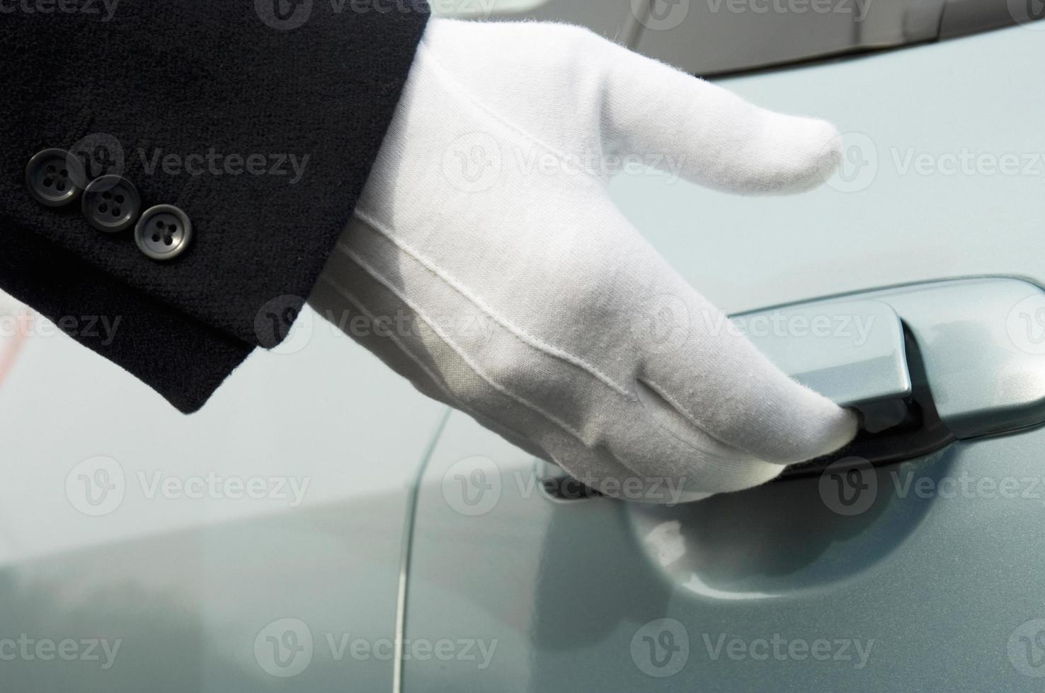 Porte de voiture ouvrant à la main en uniforme blanc photo
