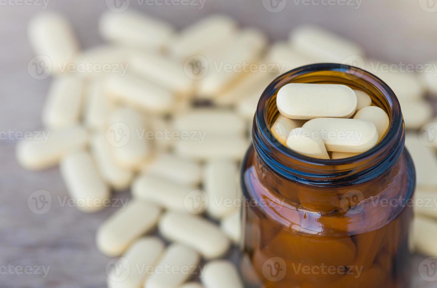 Pilules ou vitamine dans des flacons de médicaments sur fond de bois photo
