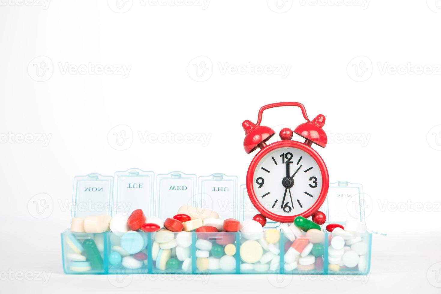 Réveil rouge et médecine dans une boîte à pilules hebdomadaire photo