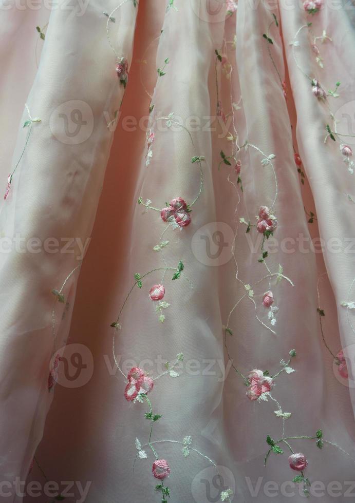 détail de robe rose transparent avec fleurs brodées photo