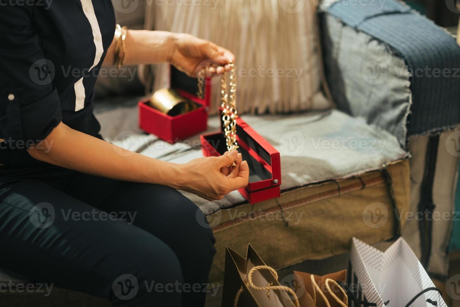 Gros plan sur la jeune femme avec des sacs de déballage de bijoux photo