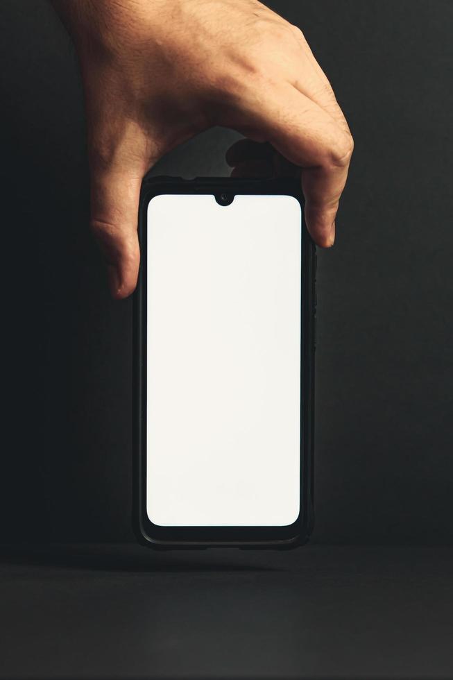 main saisissant un téléphone vierge par le haut photo