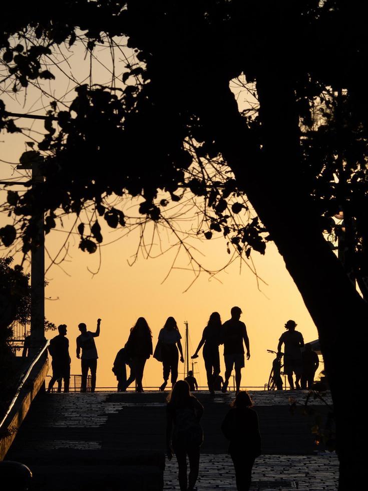 personnes marchant au coucher du soleil photo