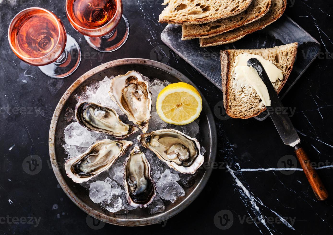 huîtres ouvertes, pain au beurre et vin rosé photo