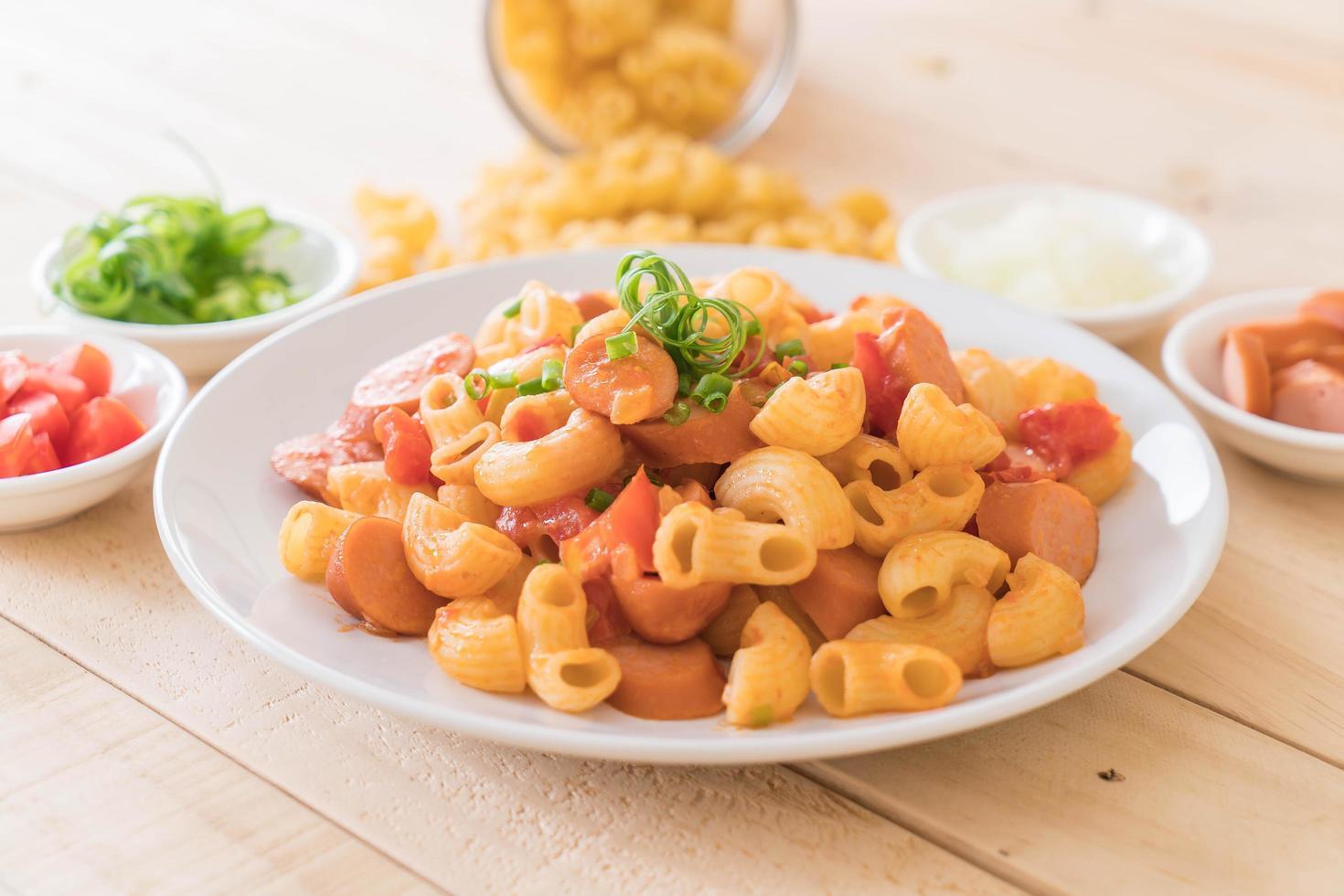 Saucisse et plat de macaroni sur table en bois photo
