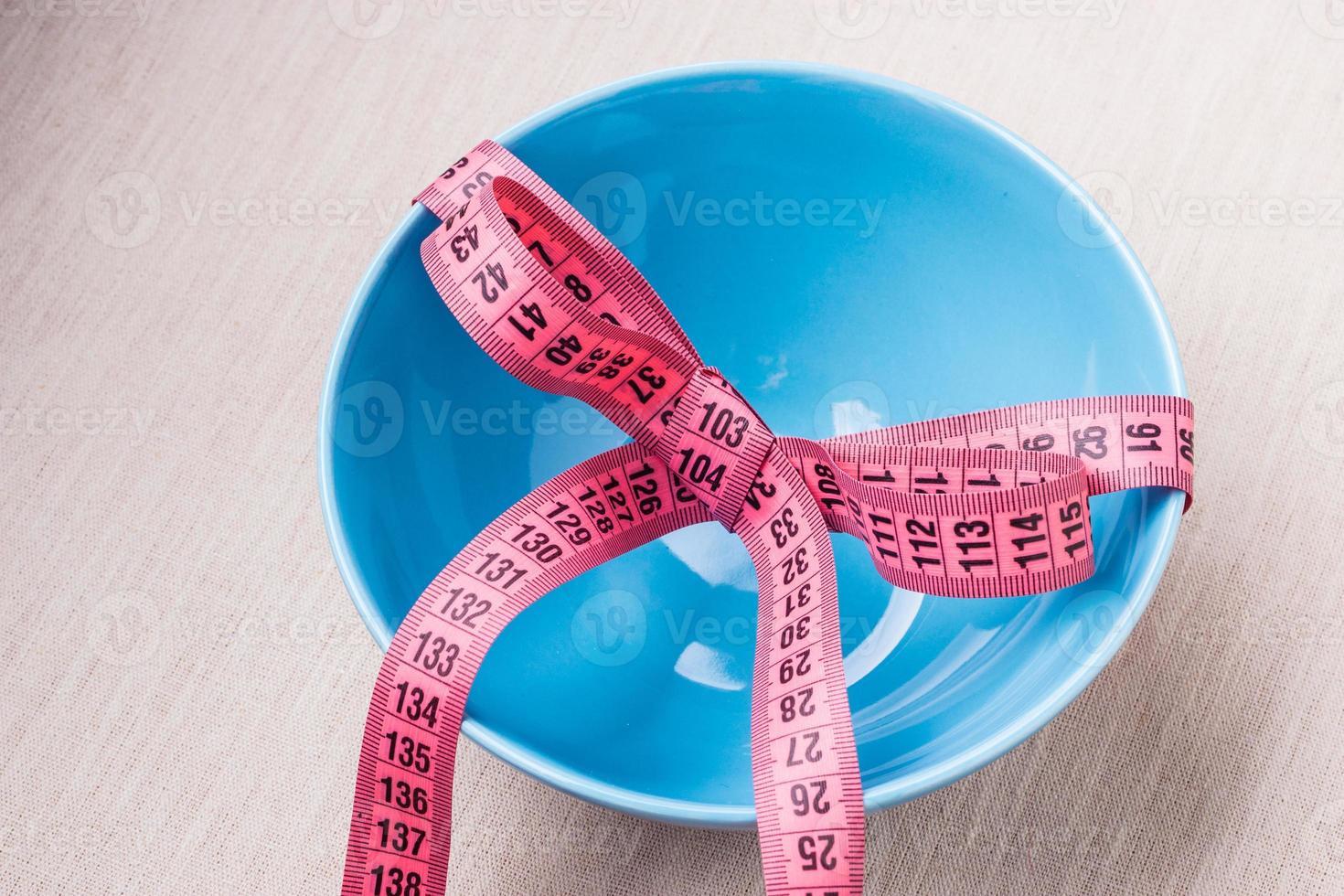 Ruban à mesurer autour d'un bol vide sur la table photo
