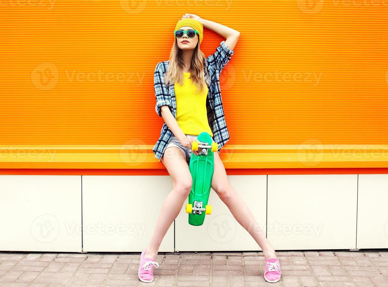 fashion hipster cool girl en lunettes de soleil et vêtements colorés avec photo