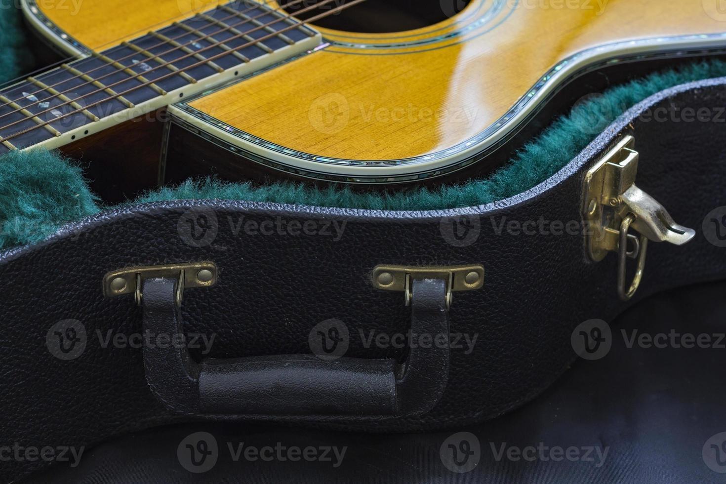 partie de guitare acoustique avec un étui de guitare ouvert. photo