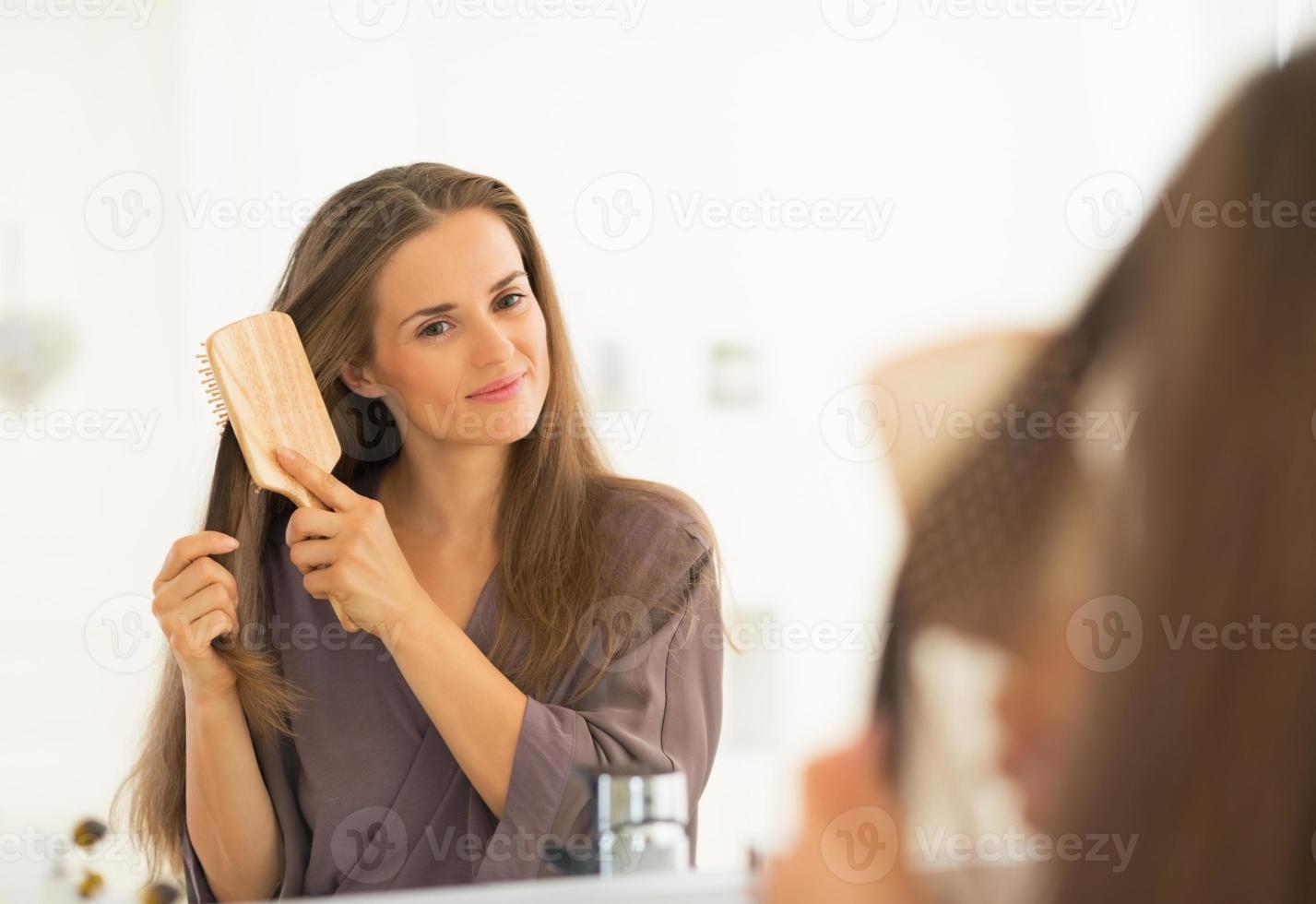 jeune femme, peigner les cheveux, dans, salle bains photo