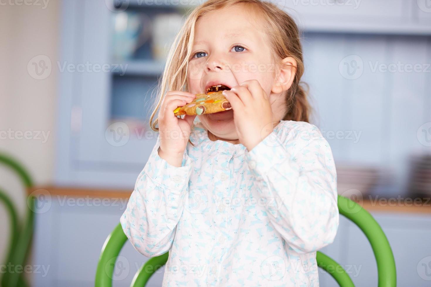 jeune fille assise à table manger des biscuits photo