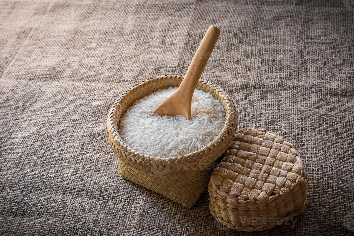 cuillères en bois et panier de riz au jasmin sur bois photo