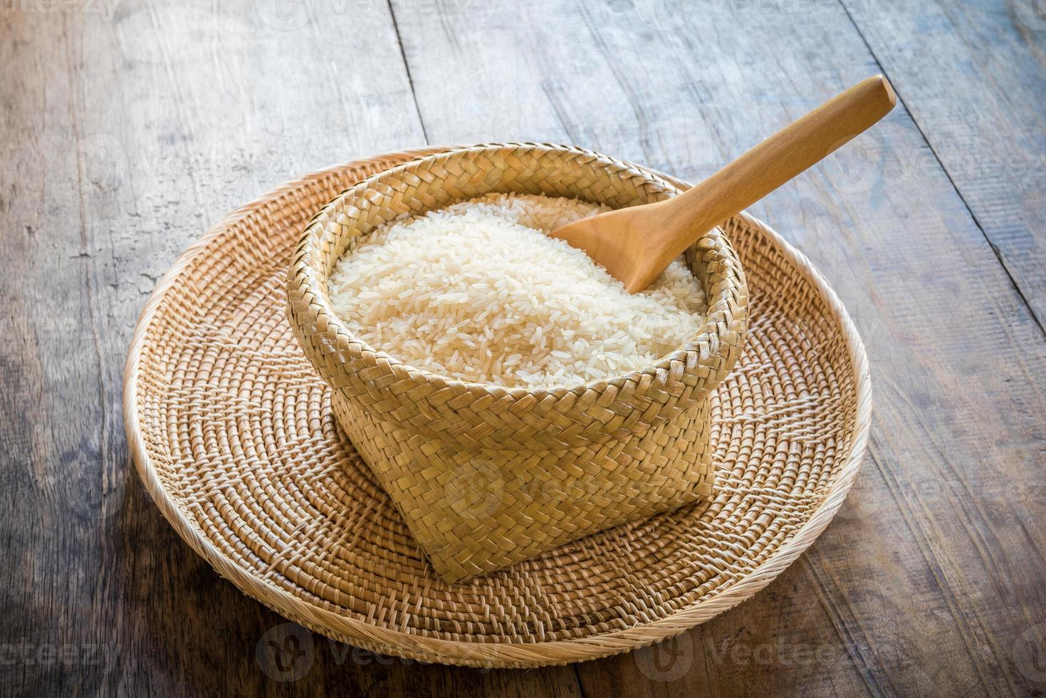 Cuillère en bois dans un panier de riz au jasmin sur bois photo