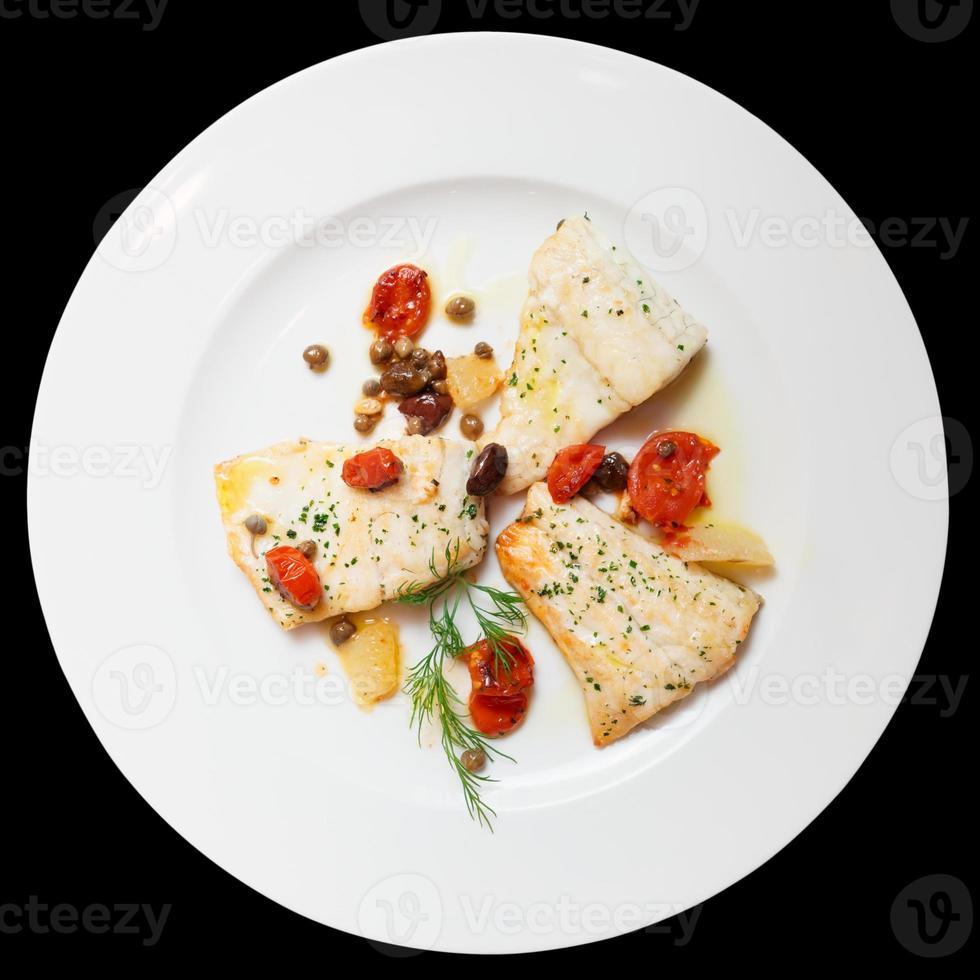 Filet de poisson frit aux câpres isolé sur noir photo