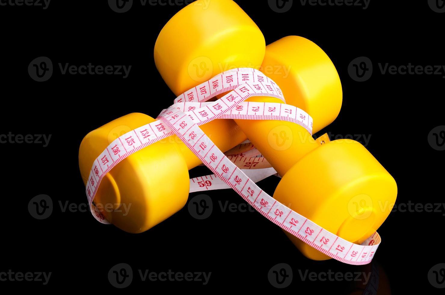 Deux haltères jaunes et ruban à mesurer allongé sur un fond noir photo