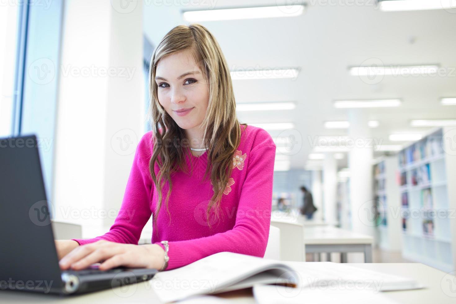femme sur ordinateur portable travaillant dans la bibliothèque photo