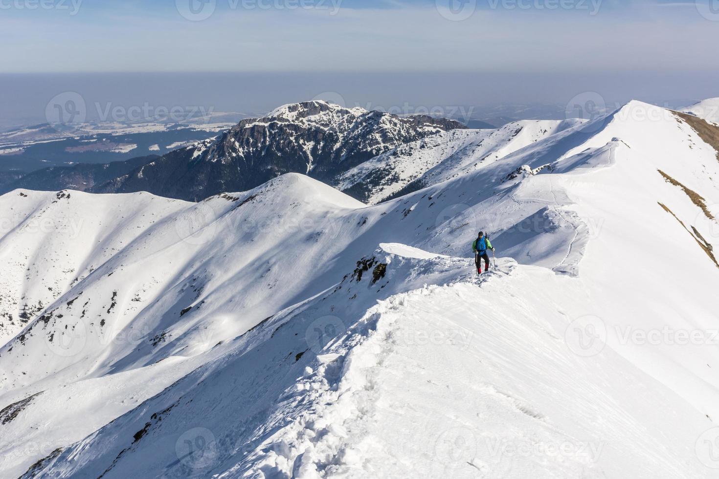 alpiniste sur la crête en conditions hivernales photo