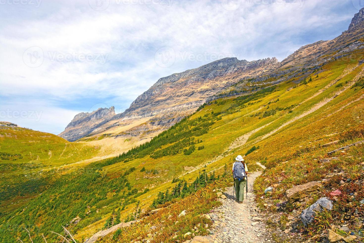 randonneur se dirigeant vers une vallée alpine à l'automne photo