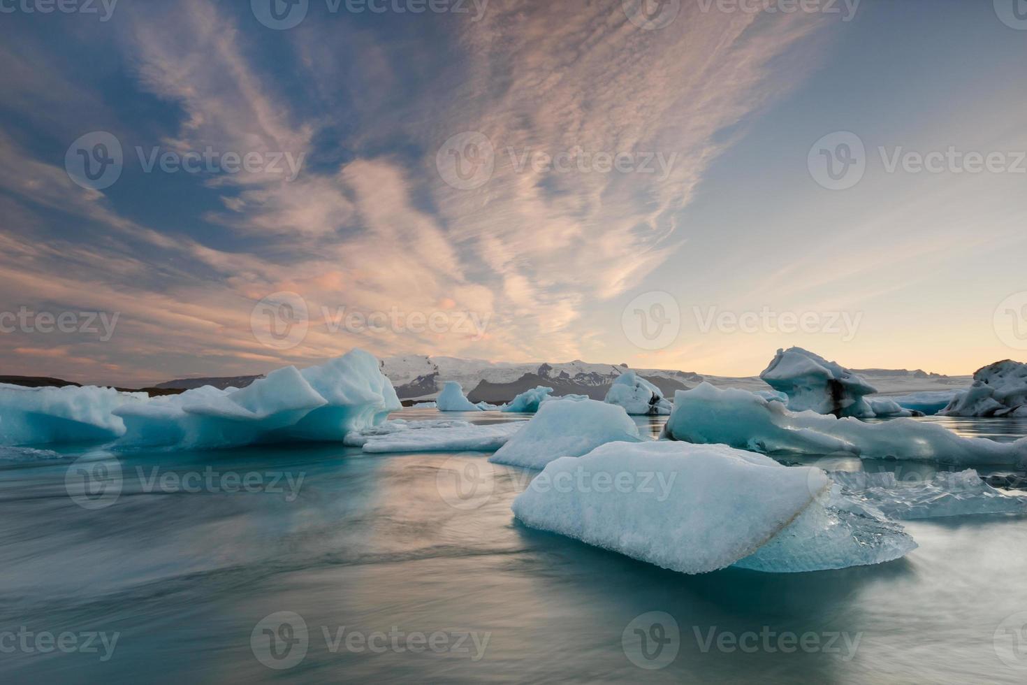 Icebergs dans le lac glaciaire de Jokulsarlon au coucher du soleil photo