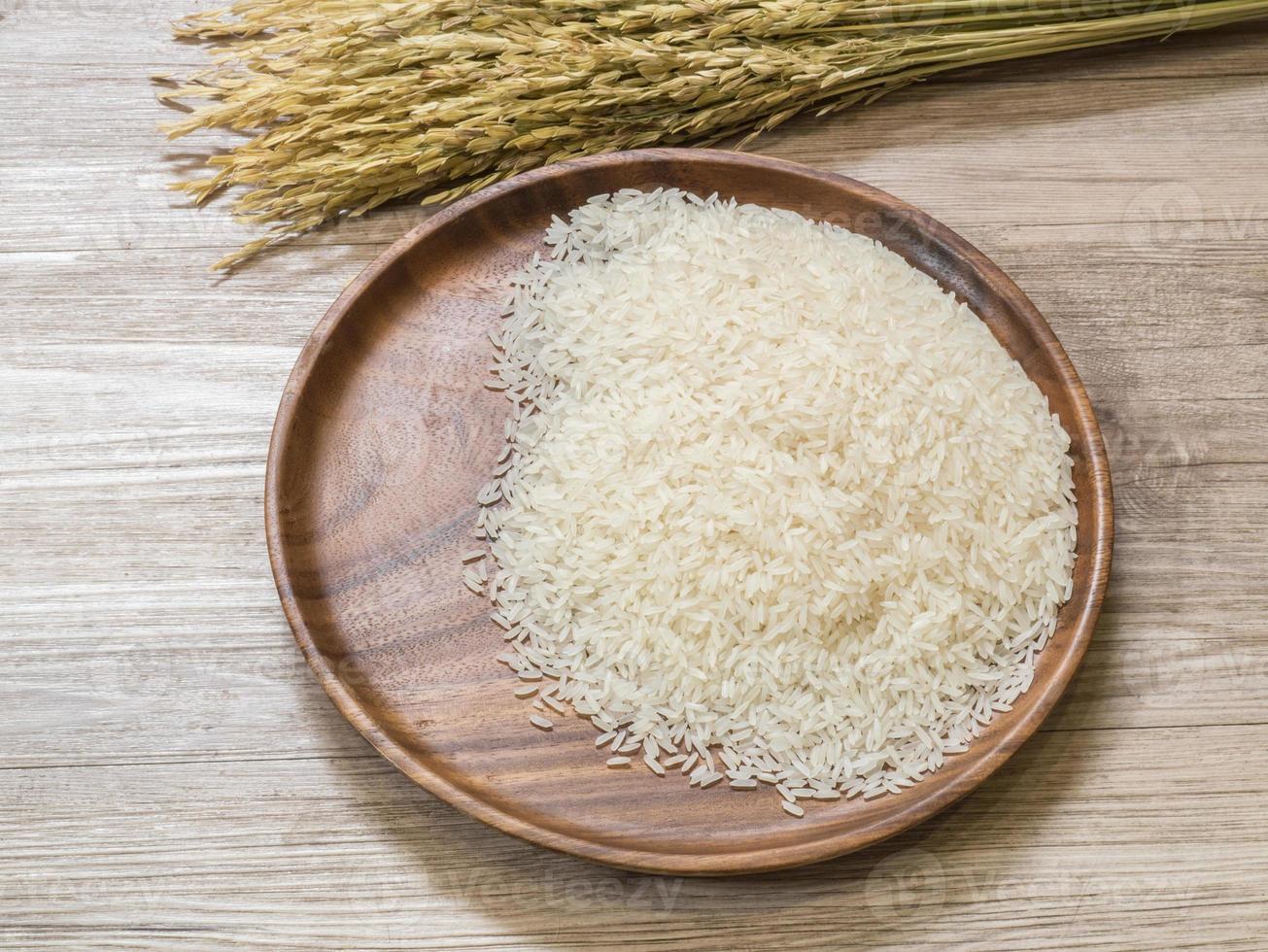 riz blanc sur la plaque en bois et plant de riz photo