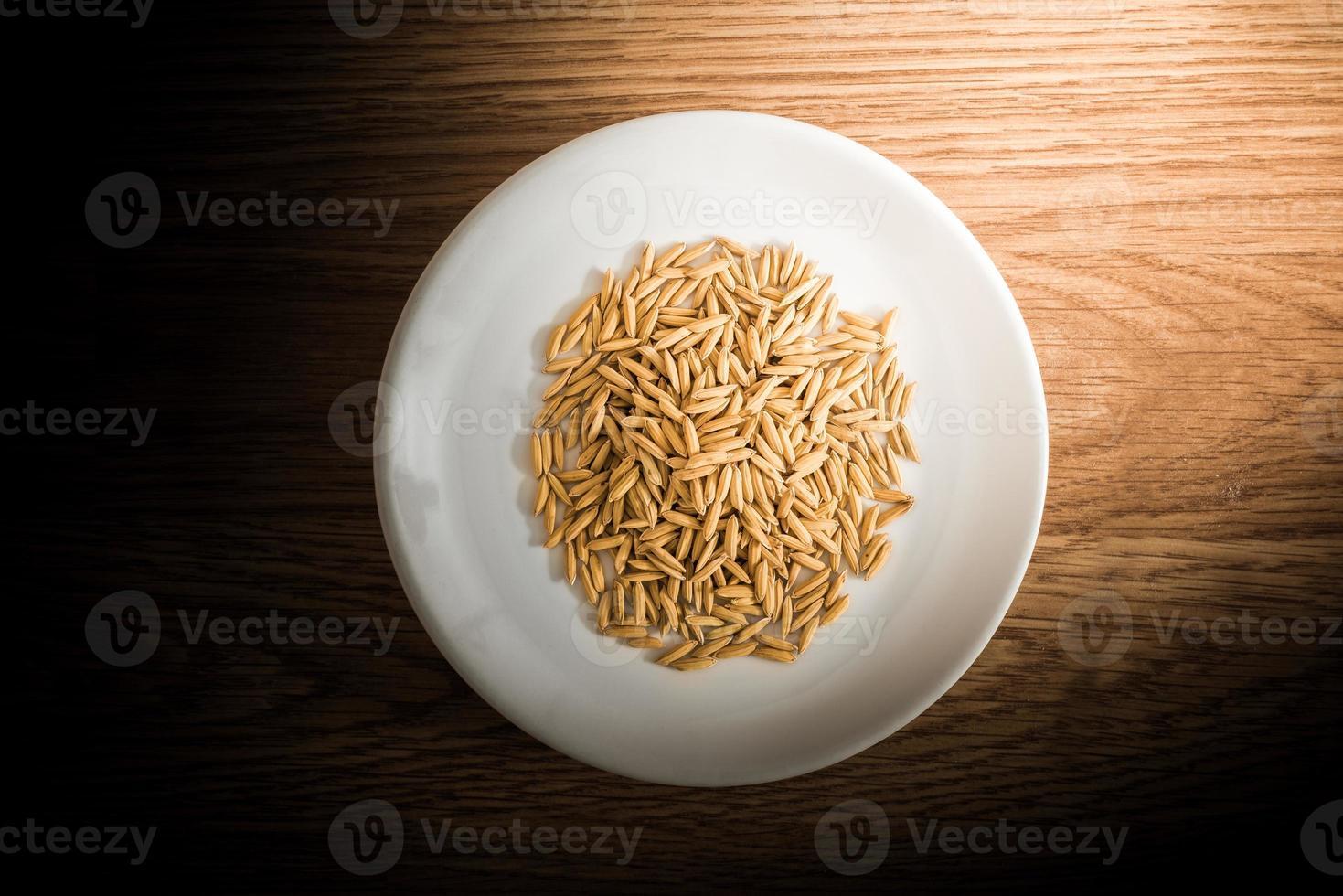 riz paddy en plaque blanche sur fond de bois photo