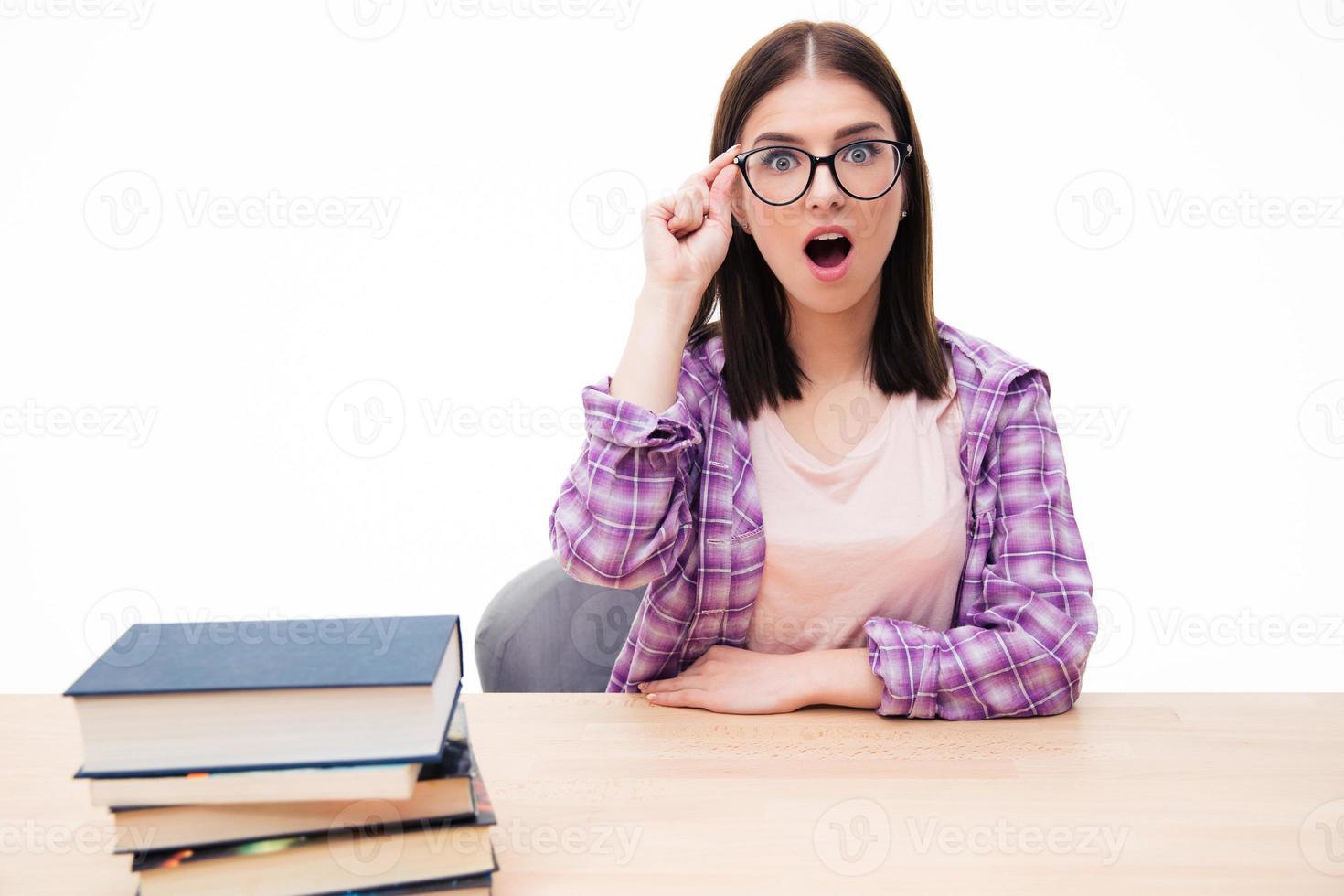 surpris, femme assise à table avec des livres photo