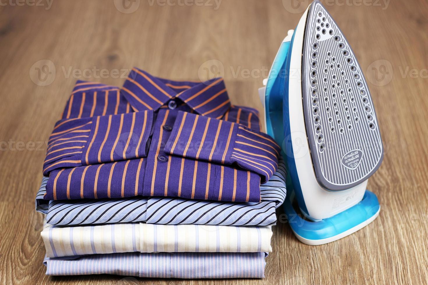 tas de chemises à repasser et main photo