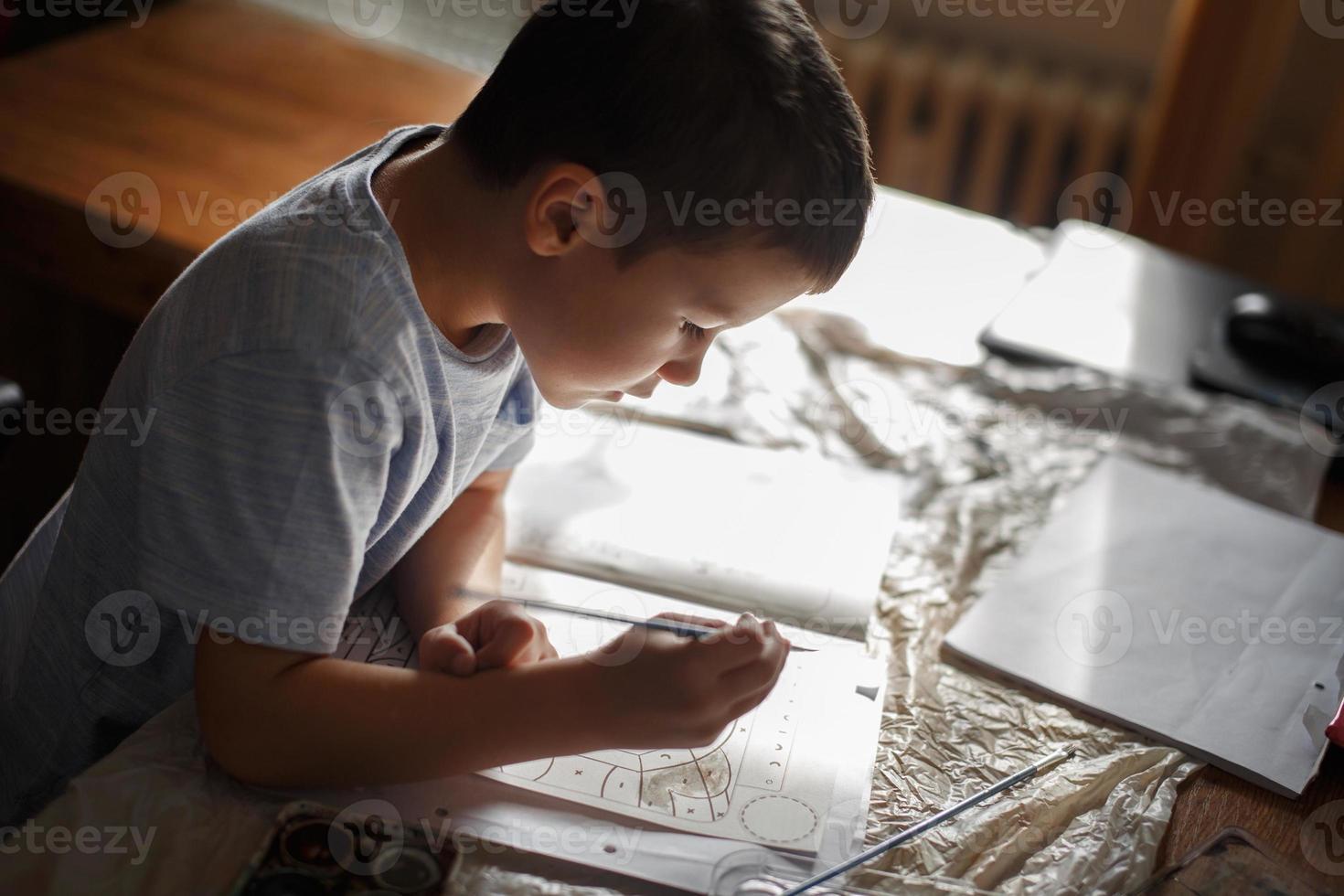 petit garçon peinture livre de coloriage à la maison photo