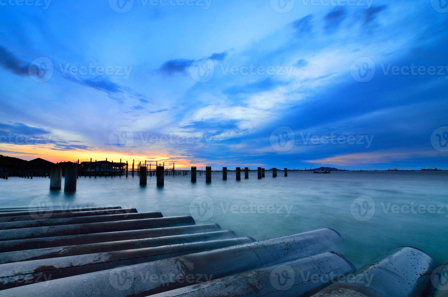 ciel coucher de soleil avec colonne de pont dans la mer photo